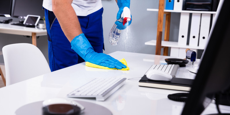 Janitorial staff sanitizing office desk in Texas